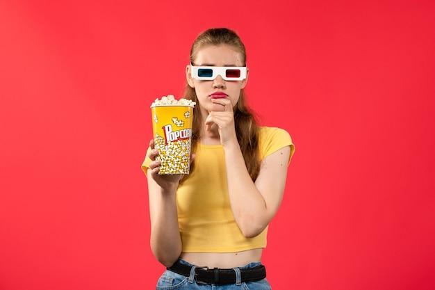Widok z przodu młoda kobieta w kinie trzymając popcorn in -d okulary i myśli na czerwonej ścianie kino kino kino zabawa film