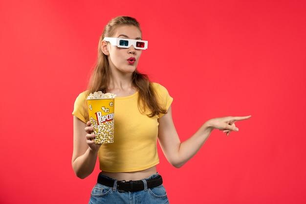 Widok z przodu młoda kobieta w kinie trzymając popcorn in -d okulary na czerwonej ścianie kino kino kino zabawa film