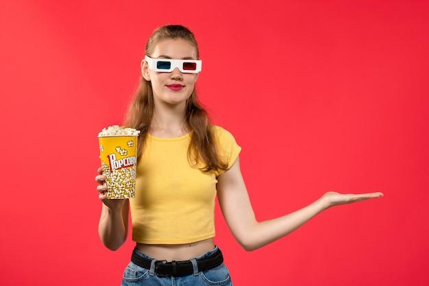 Widok z przodu młoda kobieta w kinie trzymając popcorn na czerwonej ścianie filmy teatr kino przekąska kobieta film zabawa