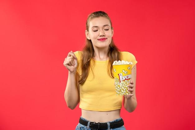 Widok z przodu młoda kobieta w kinie trzymając popcorn na czerwonej ścianie kino kino kobieta kolor