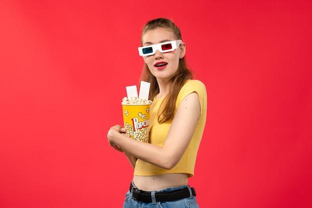 Widok z przodu młoda kobieta w kinie trzymając popcorn na jasnoczerwonej powierzchni kino kino kobiet kolory