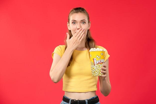 Widok z przodu młoda kobieta w kinie trzymając popcorn na jasnoczerwonej ścianie kino kino kobieta kolor