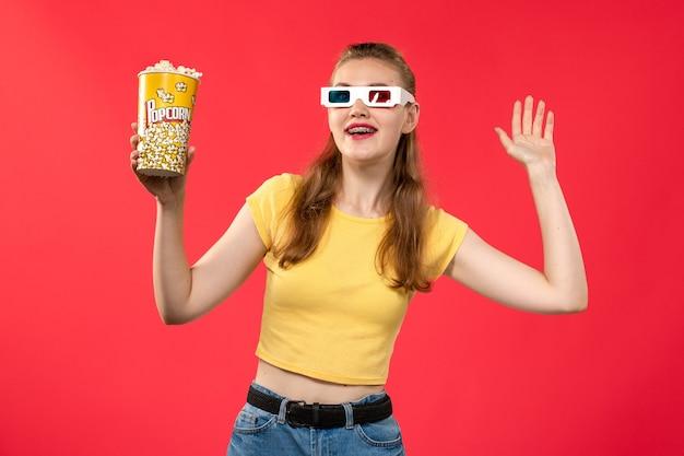 Widok z przodu młoda kobieta w kinie trzymając popcorn w d okulary przeciwsłoneczne na czerwonej ścianie kino kino kobieta zabawa czas film