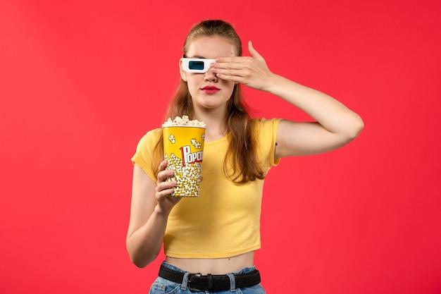 Widok z przodu młoda kobieta w kinie trzymająca popcorn in -d okulary na jasnoczerwonej ścianie kino kino przekąska film zabawa