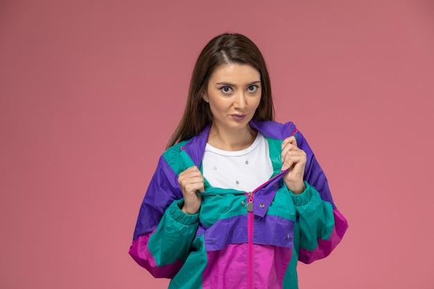 Widok z przodu młoda kobieta w kolorowym nowoczesnym płaszczu pozuje na różowej ścianie, kolorowe zdjęcie moda kobieta ubrania