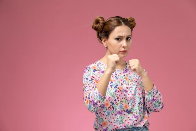 Widok z przodu młoda kobieta w koszuli zaprojektowanej w kwiatki i niebieskie dżinsy w boksie stanąć na różowym tle