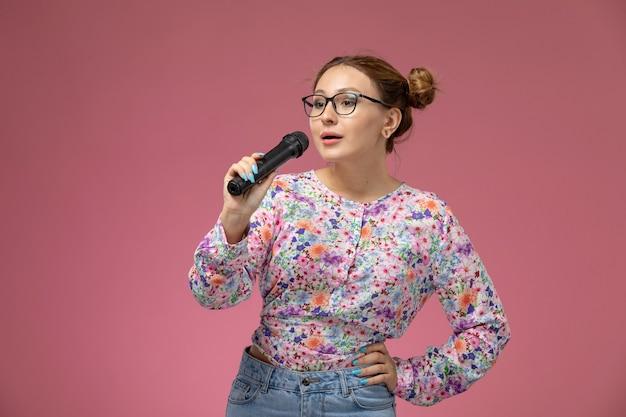 Widok z przodu młoda kobieta w koszuli zaprojektowanej w kwiatki trzymając mikrofon śpiewający na różowym tle