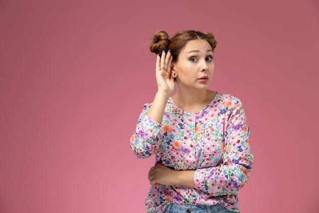 Widok z przodu młoda kobieta w koszuli zaprojektowanej w kwiaty i niebieskie dżinsy, próbując usłyszeć na różowym tle