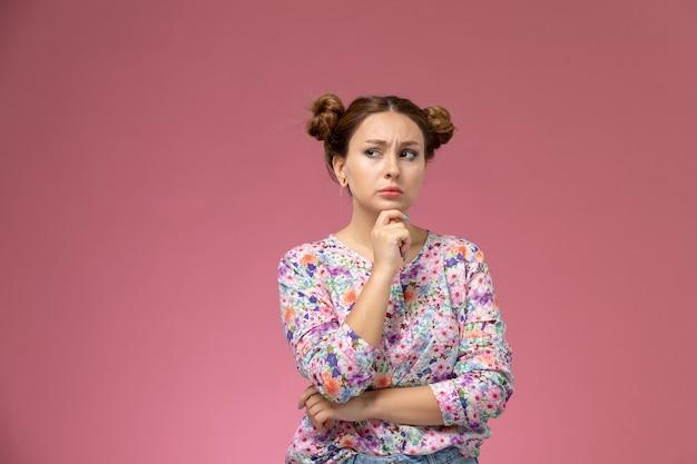 Widok z przodu młoda kobieta w kwiatowej koszuli i niebieskich dżinsach posign z myślącym wyrazem na różowym tle