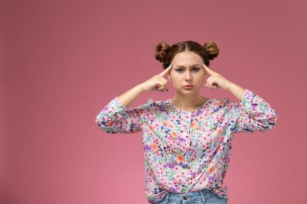 Widok z przodu młoda kobieta w kwiatowej koszuli i niebieskich dżinsach pozuje i myśli na różowym tle
