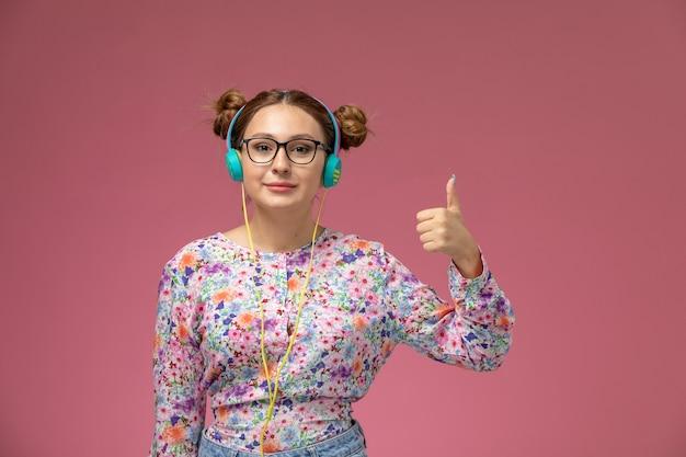 Widok z przodu młoda kobieta w kwiatowej koszuli i niebieskich dżinsach, słuchając muzyki z uśmiechem na różowym tle