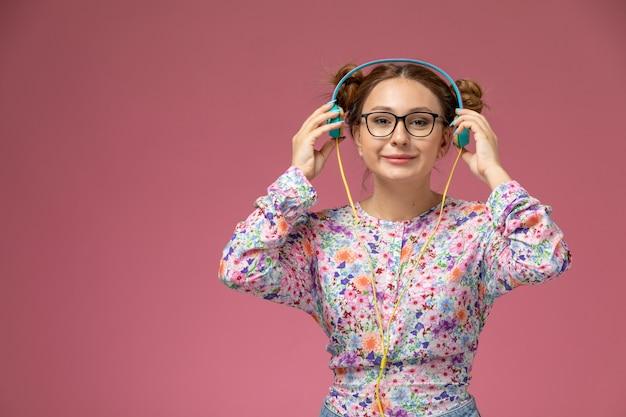 Widok z przodu młoda kobieta w kwiatowej koszuli i niebieskich dżinsach, słuchanie muzyki przez słuchawki na różowym tle