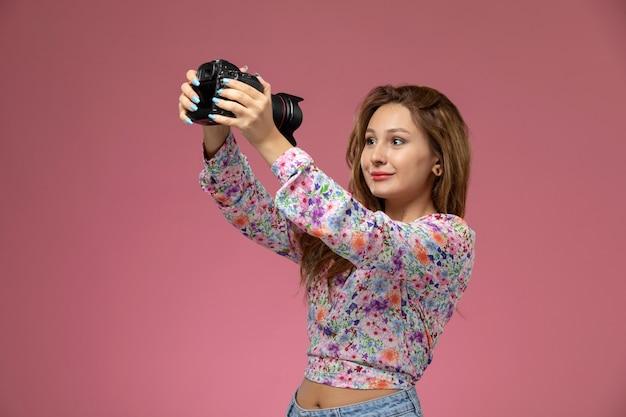 Widok z przodu młoda kobieta w kwiatowej koszuli i niebieskich dżinsach uśmiecha się i trzyma aparat fotograficzny na różowym tle