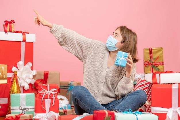 Widok z przodu młoda kobieta w masce siedzi wokół świątecznych prezentów