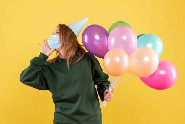 Widok z przodu młoda kobieta w masce trzymając kolorowe balony