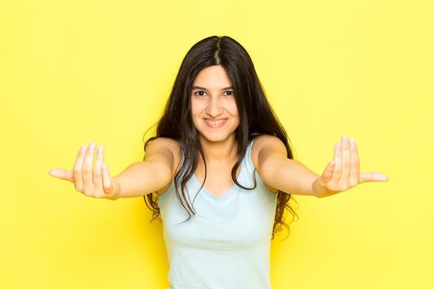 Widok z przodu młoda kobieta w niebieskiej koszuli pozowanie i woła z uśmiechem na twarzy