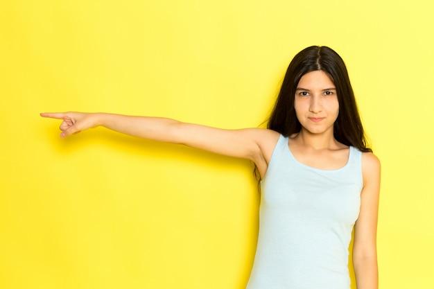 Widok z przodu młoda kobieta w niebieskiej koszuli pozowanie i wskazując palcem z gniewnym wyrazem na żółtym tle dziewczyna stanowi model piękna młoda