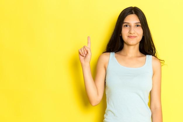 Widok z przodu młoda kobieta w niebieskiej koszuli stwarzających i msiling na żółtym tle dziewczyna stanowi model piękna młoda