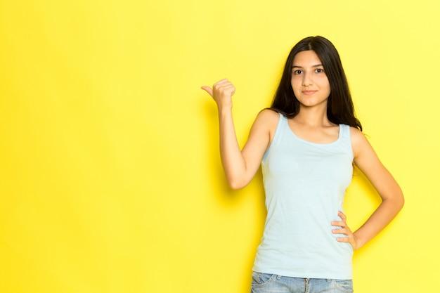 Widok z przodu młoda kobieta w niebieskiej koszuli stwarzających i wskazując palcami na żółtym tle dziewczyna stanowi model piękna młoda