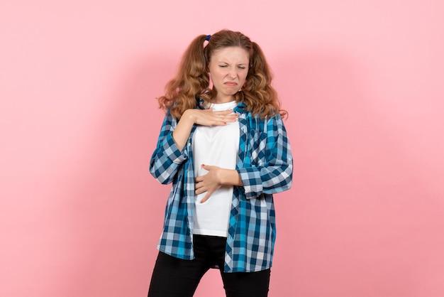 Widok z przodu młoda kobieta w niebieskiej koszuli w kratkę mająca problemy z oddychaniem na różowej ścianie młodzieżowa emocja dziewczyna dzieciak model moda