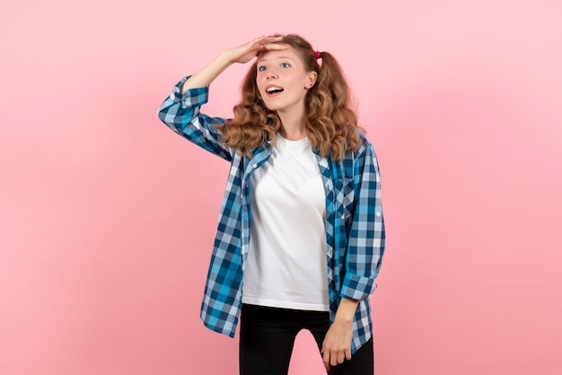 Widok z przodu młoda kobieta w niebieskiej koszuli w kratkę pozowanie na różowym tle emocje młodzieży dziewczyna dziecko modelka