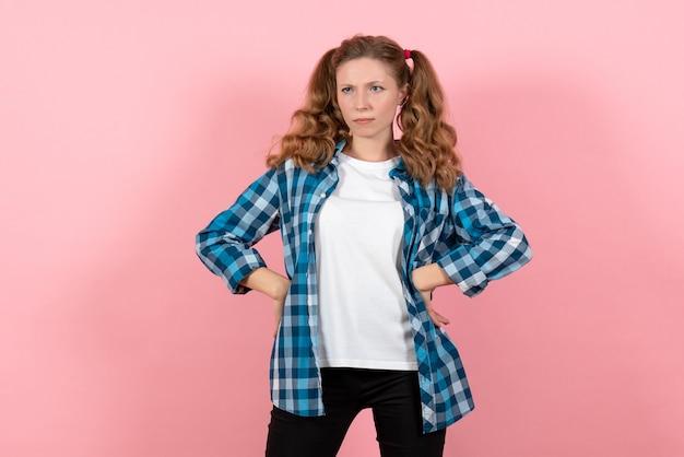 Widok z przodu młoda kobieta w niebieskiej koszuli w kratkę pozowanie na różowym tle emocje młodzieży dziewczyna modelka moda dziecięca