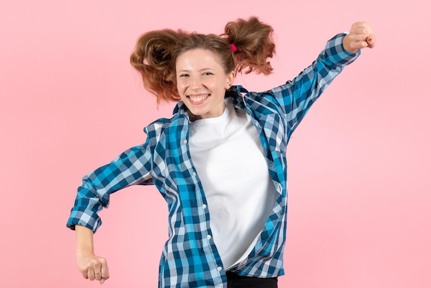 Widok z przodu młoda kobieta w niebieskiej koszuli w kratkę skacząca na różowej ścianie kobieta emocje model moda dziewczyny kolor