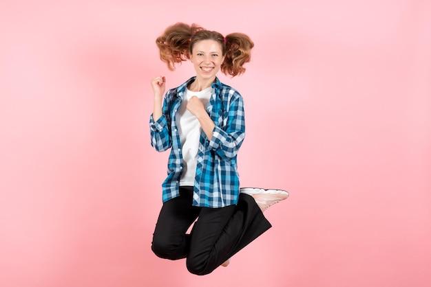 Widok z przodu młoda kobieta w niebieskiej koszuli w kratkę skacząca na różowej ścianie kobieta ludzkie emocje modelka moda dziewczyna