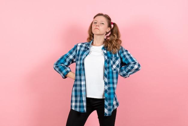 Widok z przodu młoda kobieta w niebieskiej koszuli w kratkę stwarzających na różowym tle emocje młodzieży dziewczyna dzieciak moda model