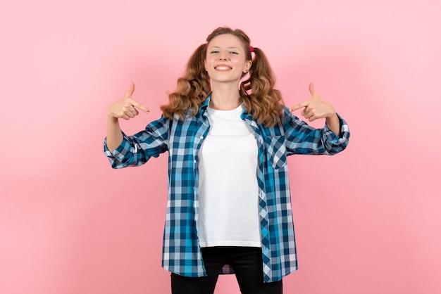 Widok z przodu młoda kobieta w niebieskiej kraciastej koszuli na różowej ścianie młodzieżowe emocje dziewczyna dziecko modelka moda