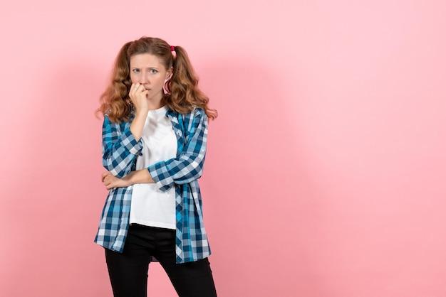 Widok z przodu młoda kobieta w niebieskiej kraciastej koszuli pozuje i myśli na różowej ścianie dziecko dziewczyna młodzieżowe emocje modelka moda
