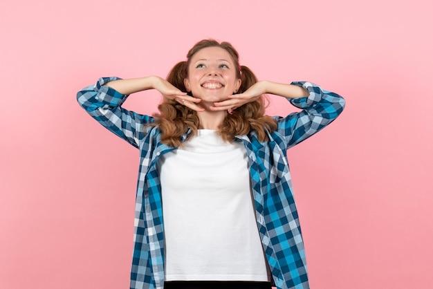 Widok z przodu młoda kobieta w niebieskiej kraciastej koszuli pozuje i uśmiecha się na różowej ścianie kobieta emocje model moda dziewczyny kolor