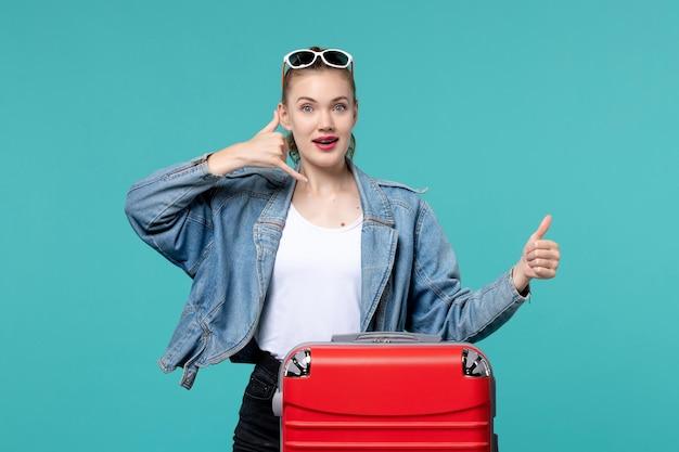 Widok z przodu młoda kobieta w niebieskiej kurtce przygotowuje się do podróży i pozuje na jasnoniebieskiej przestrzeni
