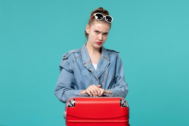 Widok z przodu młoda kobieta w niebieskiej kurtce przygotowuje się do podróży smutna na niebieskiej przestrzeni