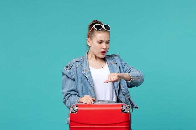 Widok z przodu młoda kobieta w niebieskiej kurtce, szykując się do podróży i sprawdzania czasu na niebieskiej przestrzeni