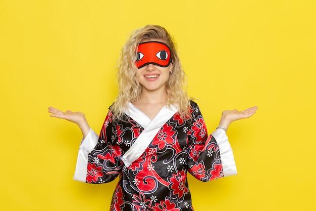 Widok z przodu młoda kobieta w nocnej szacie i noszącej maskę na oczy przygotowuje się do spania na żółtej ścianie nocny sen kobiet w ciemnym kolorze