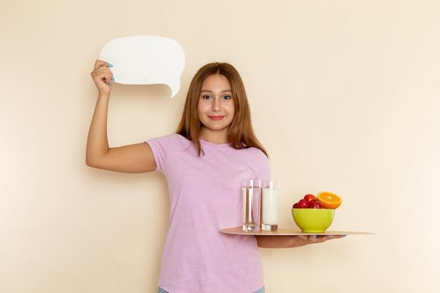 Widok z przodu młoda kobieta w różowej koszulce trzymając tacę owoce mleko i wodę na szaro