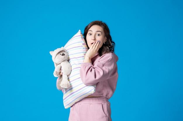 Widok z przodu młoda kobieta w różowej piżamie z małym misiem-zabawką i poduszką na niebieskim łóżku noc koszmar sen kobieta odpoczynek impreza marzeń