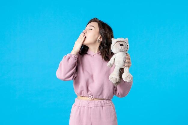 Widok z przodu młoda kobieta w różowej piżamie z małym misiem-zabawką na niebieskim kolorze snu sen bezsenność łóżko kobieta odpoczynek