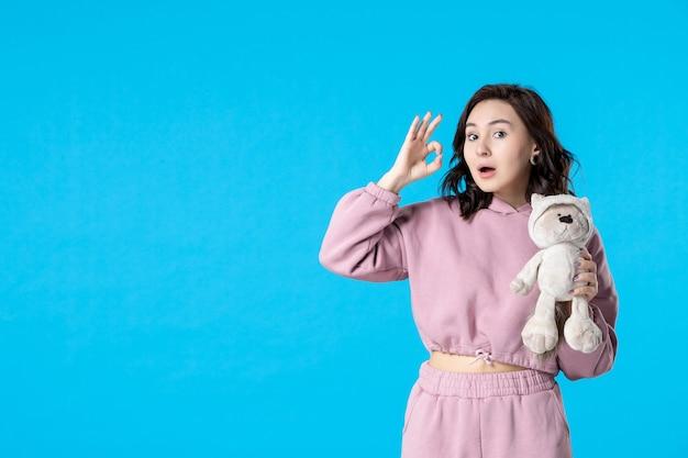 Widok z przodu młoda kobieta w różowej piżamie z małym misiem-zabawką w kolorze bluesleep dream