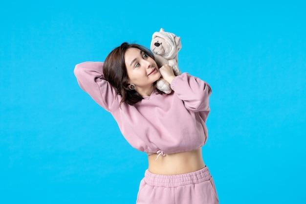 Widok z przodu młoda kobieta w różowej piżamie z małym pluszowym misiem na bluesleep dream color reszta bezsenności kobieta party