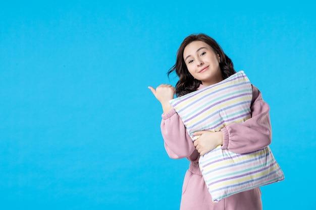 Widok z przodu młoda kobieta w różowej piżamie z poduszką na bluenight color party łóżko odpoczynek sen bezsenność sen