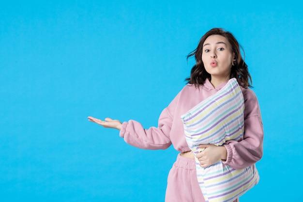 Widok z przodu młoda kobieta w różowej piżamie z poduszką na bluenight color party łóżko odpoczynek sen kobieta sen
