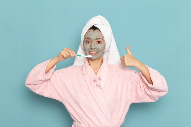 Widok z przodu młoda kobieta w różowym szlafroku po prysznicu do czyszczenia zębów na jasnoniebieskiej ścianie