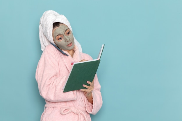 Widok z przodu młoda kobieta w różowym szlafroku po prysznicu rozmawia przez telefon czytając zeszyt na jasnoniebieskiej ścianie piękna woda samoopieka prysznic czysty