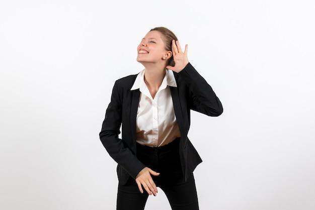 Widok z przodu młoda kobieta w ścisłym klasycznym garniturze pozowanie i słuchanie uważnie na białym tle kobieta biznesowych kobieta garnitur pracy