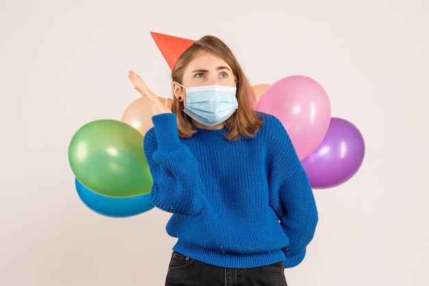 Widok z przodu młoda kobieta w sterylnej masce, chowając kolorowe balony za plecami