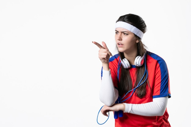Widok z przodu młoda kobieta w strojach sportowych z skakankami na białej ścianie