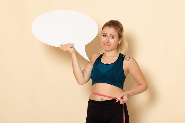 Widok z przodu młoda kobieta w stroju sportowym, trzymając biały znak i mierząc jej ciało na białej ścianie