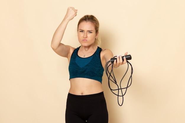 Widok z przodu młoda kobieta w stroju sportowym trzymając skakanki na białej ścianie ćwiczenia zdrowotne treningu ciała sport urody